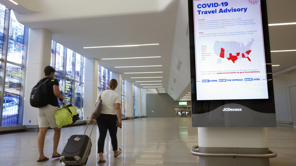 Arriving travelers walk by a COVID-19 travel advisory sign in the baggage claim area at New York City