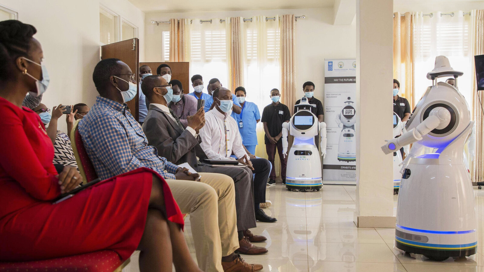 A robot introduces itself to patients in Kigali, Rwanda. The robots, used in Rwanda's treatment centers, can screen people for COVID-19 and deliver food and medication, among other tasks. The robots were donated by the United Nations Development Program and the Rwanda Ministry of ICT and Innovation. Cyril Ndegeya/Xinhua News Agency/Getty Images