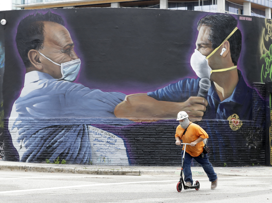 A construction worker rides a scooter Monday in Miami past a Hiero Veiga mural of businessman Moishe Mana (left) and Miami Mayor Francis X. Suarez wearing masks. (Wilfredo Lee/AP)
