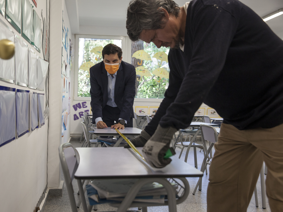 Gonzalo Inclán and Enfrén Carreño of the Liceo Europeo school just outside of Madrid, Spain measure the space between desks in May. (Miguel Pereira/Getty Images)