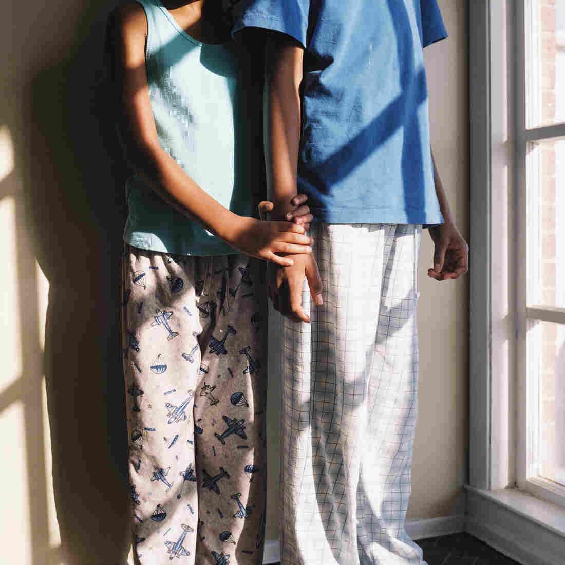 Thandi and Khaya holding each other while wearing pajamas.