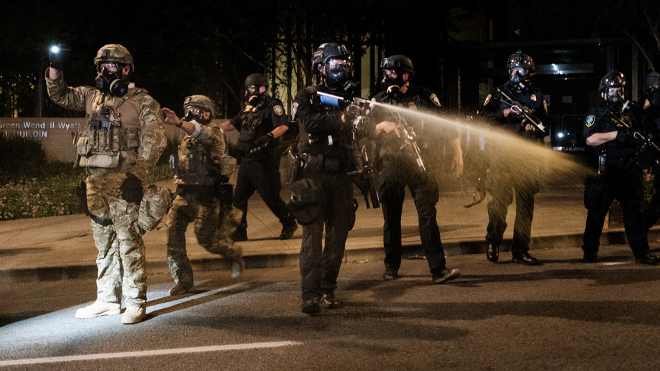 Federal officers use tear gas and other crowd dispersal munitions on protesters outside the Multnomah County Justice Center on Friday in Portland, Ore. (Mason Trinca/Getty Images)