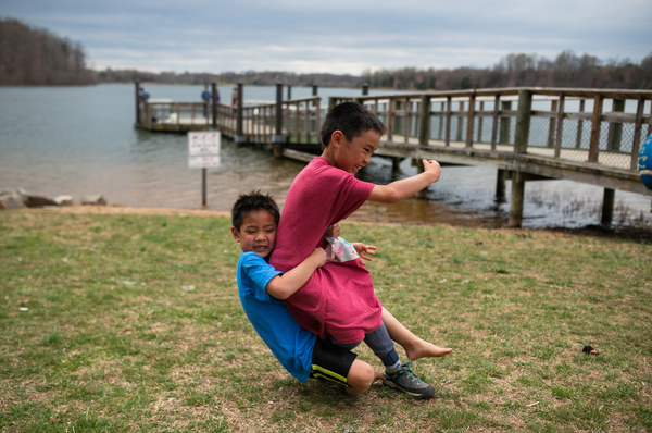 Hayle tackles Henry during a game of football Black Hill Regional Park in Boyds, Md., on April 7, 2019.