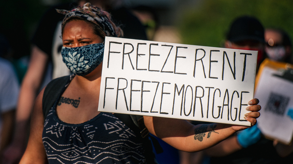 """A woman joins with other demonstrators during the """"Cancel Rent and Mortgages"""" rally in late June in Minneapolis. The march was demanding the temporary cancellation of rents and mortgages as COVID-19 batters the economy."""