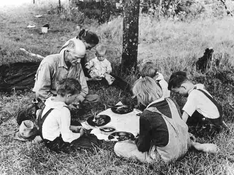 1930: A migrant family says grace before their noonday meal by the side of the road east of Oklahoma.