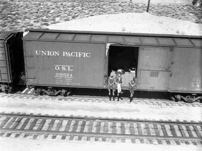 Several people ride an empty freight car to Southern California during the Great Depression.