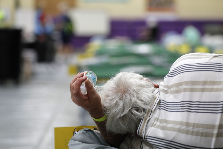An evacuee lies on a cot at an evacuation shelter for people with disabilities in Stuart, Fla., in preparation for Hurricane Dorian on Sept. 1, 2019. Now, with the pandemic raging, officials across the South are trying to adjust their evacuation and shelter plans. (Gerald Herbert/AP)
