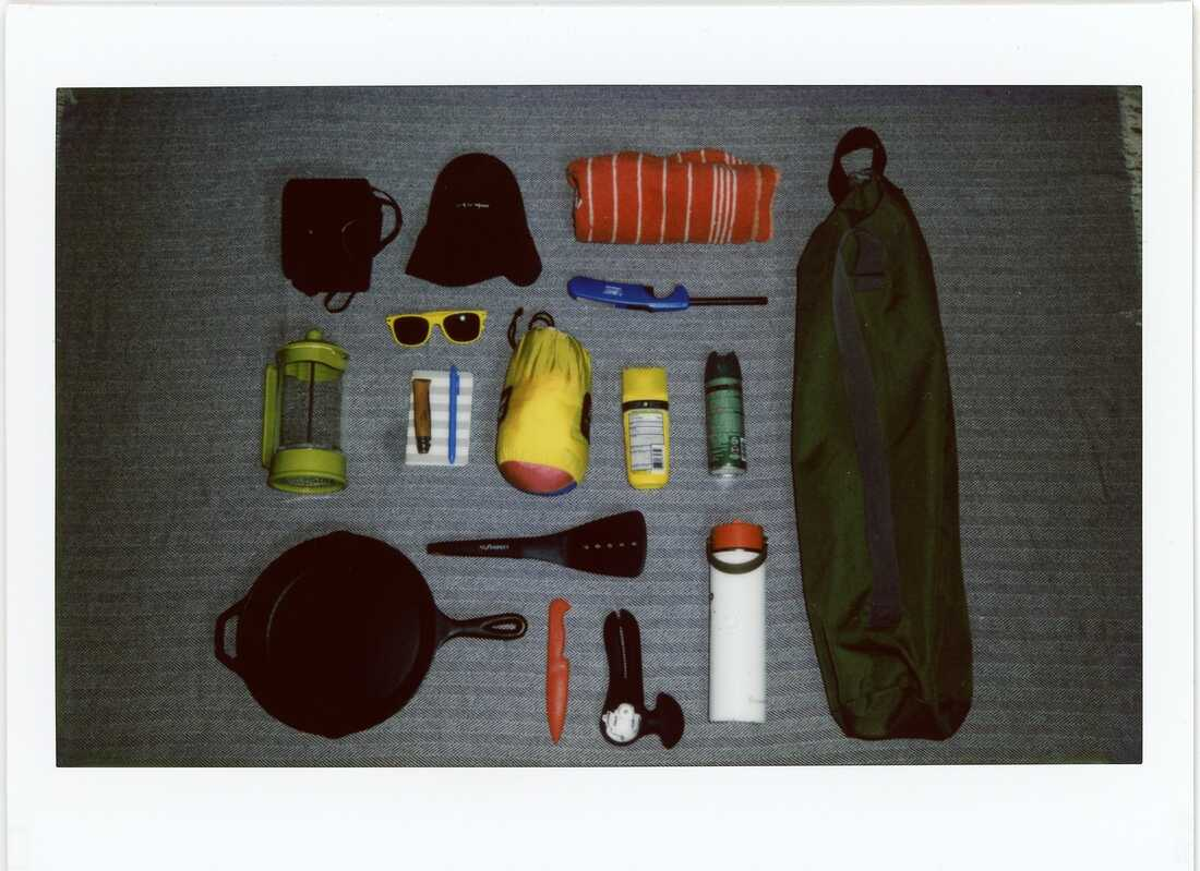 A polaroid photo of camping gear including a camping chair, sun screen, bug spray, sunglasses, a cast iron skillet, etc., arranged in a neat grid on a blue blanket.