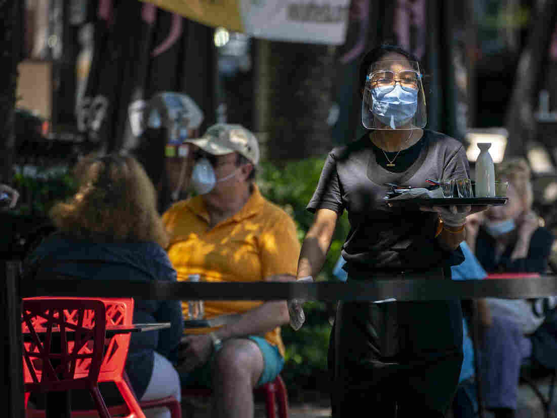 BETHESDA, MD - JUNE 12: A waiter at Raku, an Asian restaurant in Bethesda, wears a protective face mask as serve customers outdoors amid the coronavirus pandemic on June 12, 2020 in Bethesda, Maryland. Many streets are closed to vehicles in downtown Bethesda as Montgomery County continues its phase one easing of COVID-19 restrictions. (Photo by Sarah Silbiger/Getty Images)