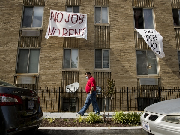 Signs hang from the windows of an apartment in Washington, D.C., on May 20. Housing advocates and landlords alike say if Congress doesn't extend or replace federal unemployment payments, millions of out-of-work Americans won't be able to afford to pay their rent.