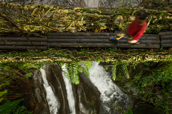 A man crosses a bridge while a river flows unhindered below. In a few bridges, the base is evened out using wooden logs, making it easier to walk across.