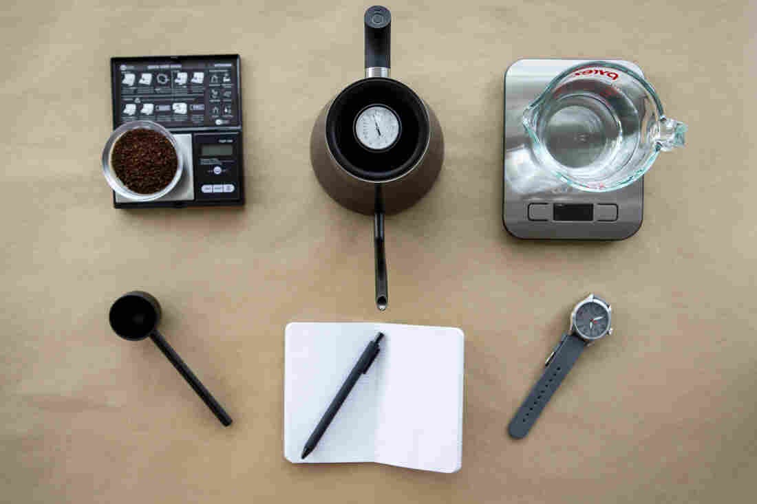 Coffee grounds on a scale, a black gooseneck kettle, water on a scale, a coffee scoop, a notebook and pen and a watch are photographed from above on a tan background.