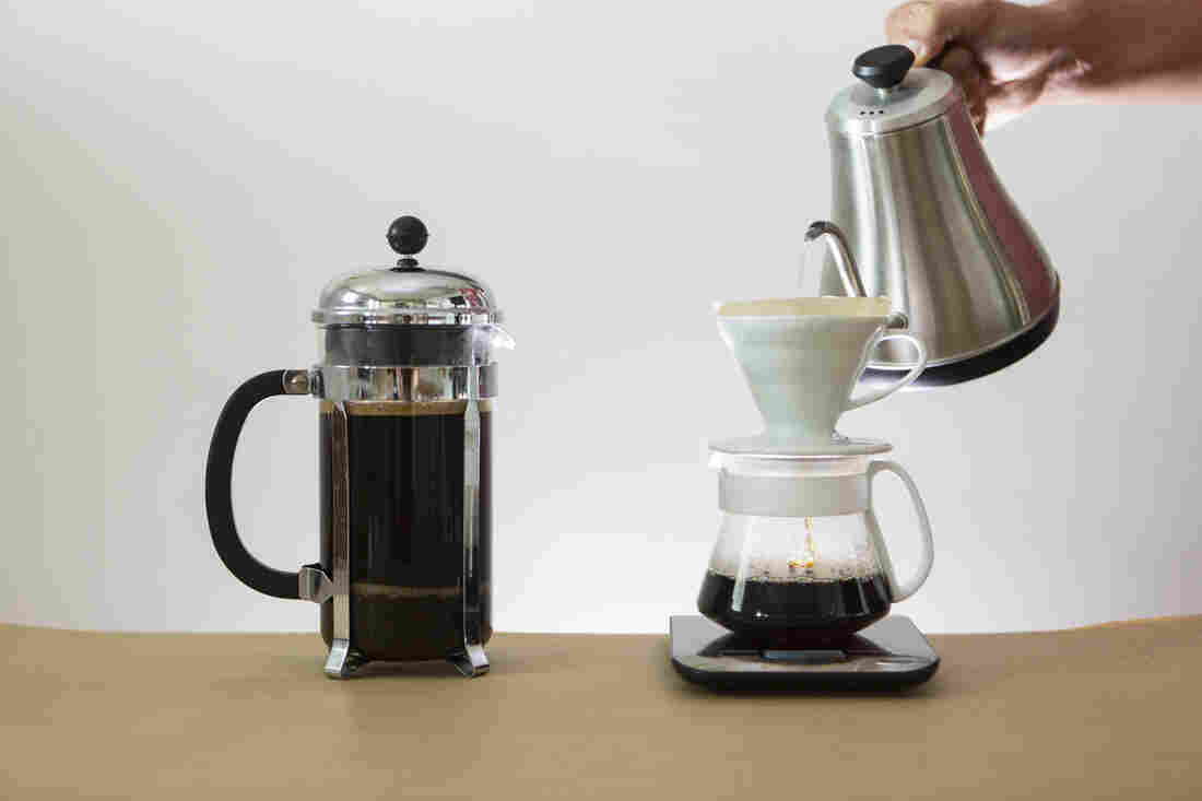 A french press full of coffee on the left and a pour over device with a hand pouring water over coffee sit on a tan table top against a white backdrop.