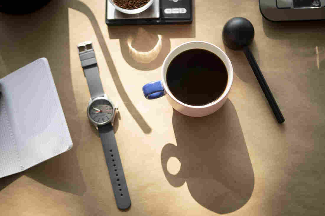 A mug full of coffee, a watch, a coffee scoop, a notebook, a scale and the shadow of a goose neck kettle are photographed from above against a tan backdrop.