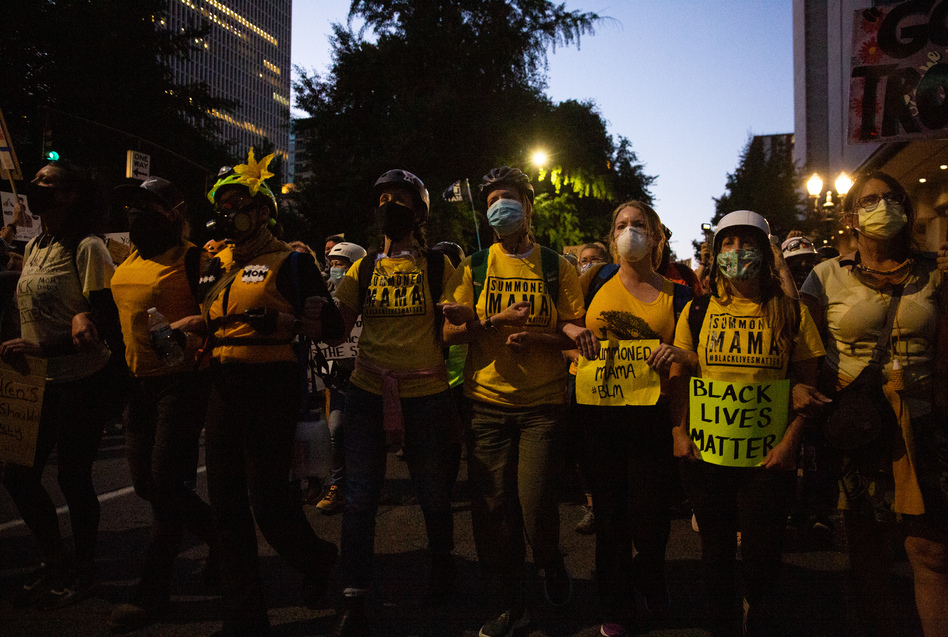 The Wall of Moms marches to the Multnomah County Justice Center in Portland, Ore., July 25, 2020. Portland has sustained protests against police brutality and systemic racism for 58 days. (Bradley W. Parks/OPB)