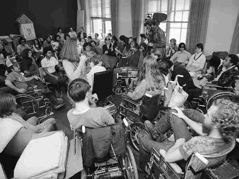 Weary demonstrators continue a sit-in at the offices of the Health, Education and Welfare department in San Francisco until civil rights rules for people with disabilities are signed, April 9th, 1977. The woman standing at left center interprets for the hearing impaired during a group briefing.