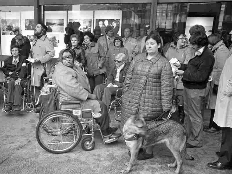 People gathering at the entrance to the John F. Kennedy Federal Building in Boston to protest the Federal Government's delay in implementing the Rehabilitation Act passed by Congress in 1973 on April 5th, 1977. The act prohibits discrimination against citizens with disabilities by any agency or institution receiving federal funds.