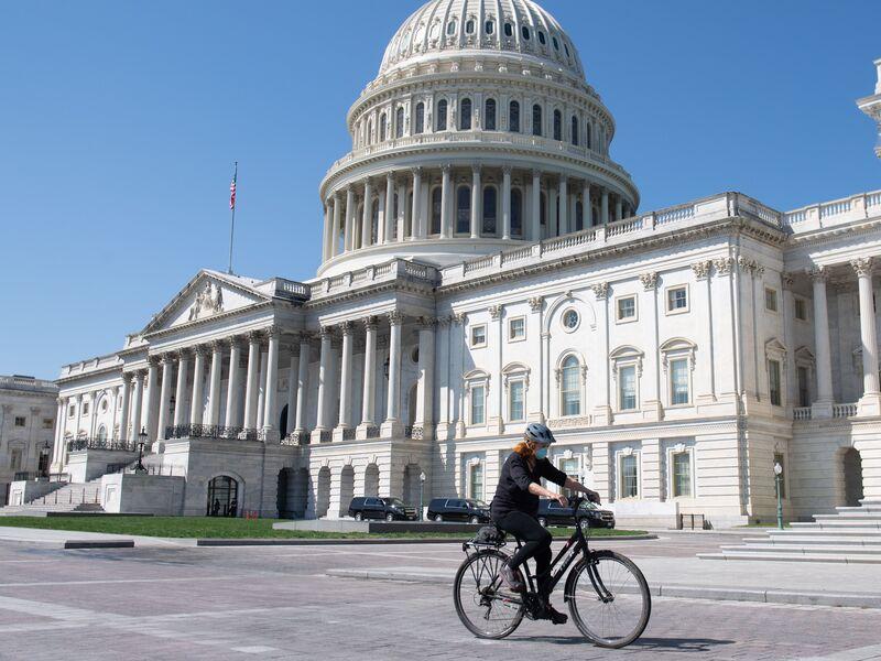 Uma mulher usando uma máscara para impedir a propagação do coronavírus anda de bicicleta em frente ao Capitólio dos EUA em Washington, DC, em 9 de abril.
