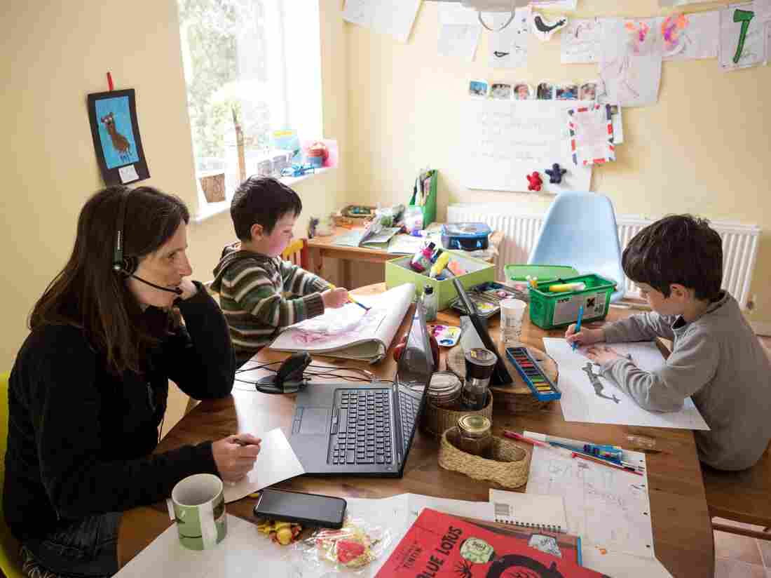 Six-year-old Leo (R) and his three-year old brother Espen (C) complete homeschooling activities suggested by the online learning website of their infant school, as his mother Moira, an employee of a regional council, works from home (Photo by OLI SCARFF/AFP via Getty Images)