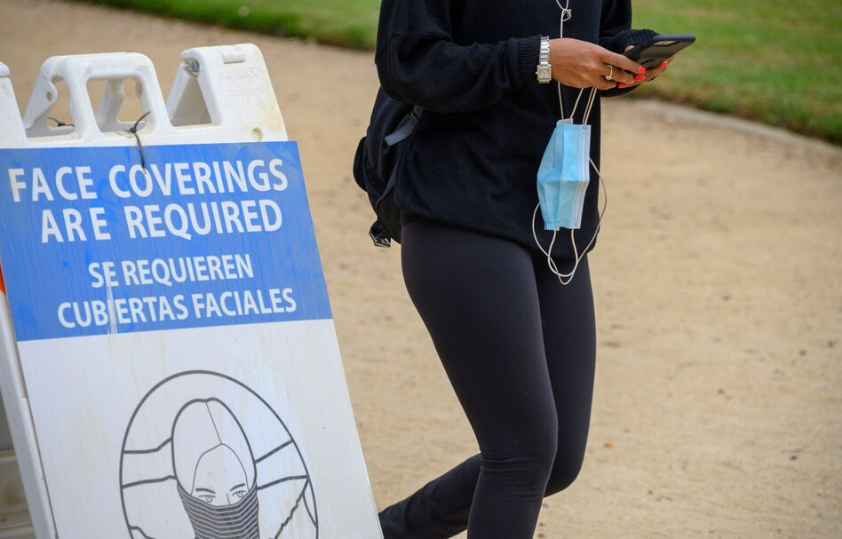 A woman carrying her mask walks past a sign mandating the wearing of face coverings in an effort to control the spread of coronavirus as she walks in Palisades Park in Santa Monica, Calif., on July 25, 2020. (Robyn Beck/AFP via Getty Images)