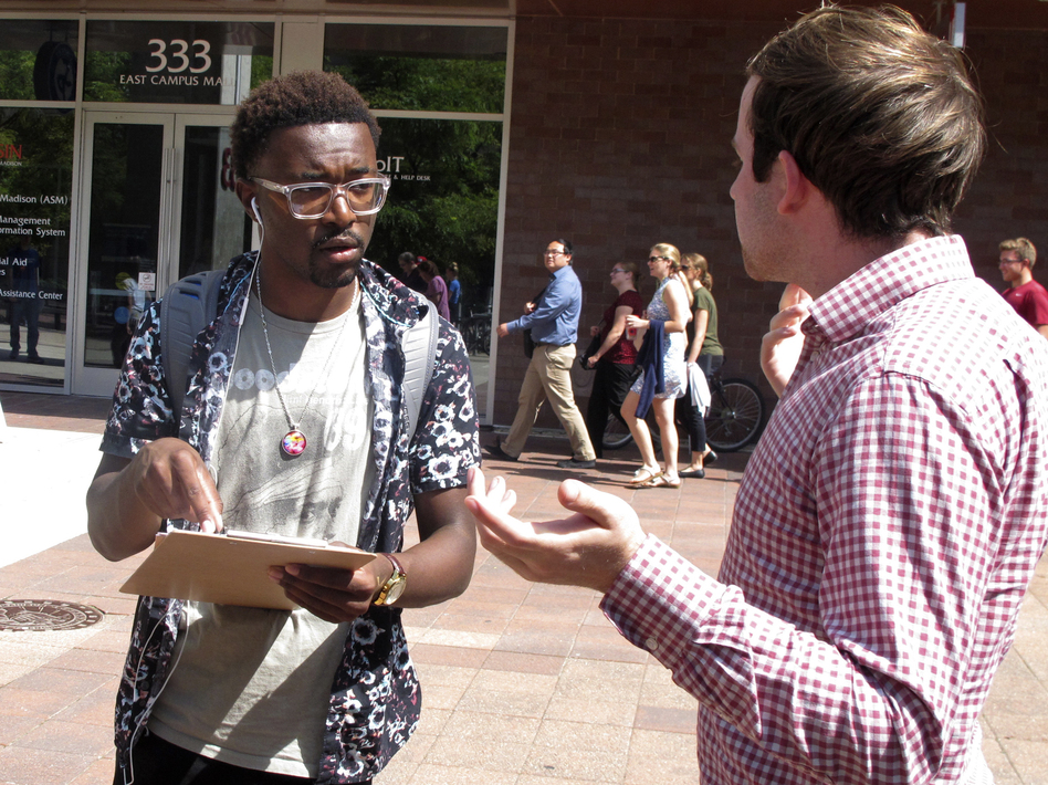 A University of Wisconsin student gets information about registering to vote from a NextGen America worker in Madison, Wis., in 2018. (Scott Bauer/AP)