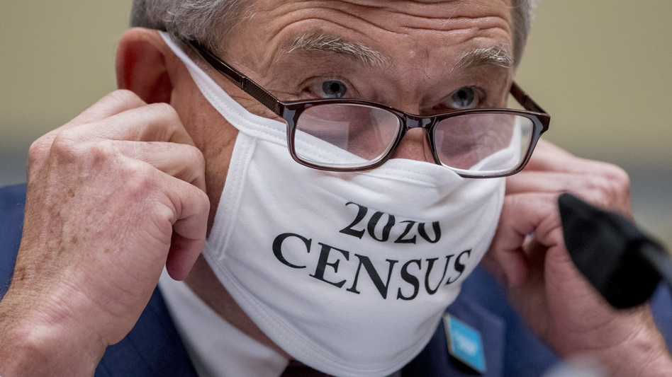 """Census Bureau Director Steven Dillingham, wearing a face covering printed with the words """"2020 Census,"""" faced questions from lawmakers Wednesday on plans for finishing the count. NPR has learned the bureau recently decided to end door knocking on Sept. 30, increasing the risk of an undercount. (Andrew Harnik/AP)"""