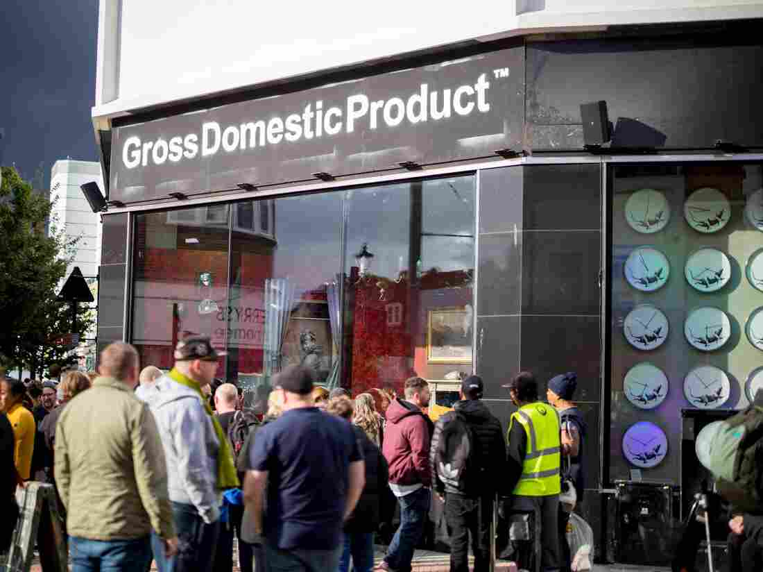 People look at a shopfront displaying a mini exhibition by secretive British artist, Banksy with the sign 'Gross Domestic Product' in Croydon, south London (TOLGA AKMEN/AFP via Getty Images)