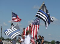 People wave thin blue line flags while they attend a Back the Blue rally in support of police departments on Quincy Shore Drive in Quincy, Mass. on June 20.