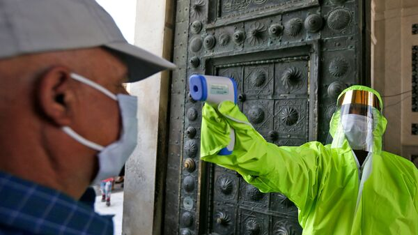A medic checks the temperature of a Syrian worshipper before entering the Umayyad Mosque in Damascus to attend Friday prayer on May 15. To try to slow the coronavirus outbreak, the Syrian government has banned mass prayers and asked Syrians to stay home over the Muslim holiday of Eid al-Adha this weekend.