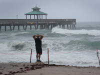 Waves kicked up by Tropical Storm Isaias crash along Deerfield Beach, Fla., on Sunday. Isaias has regained hurricane strength and expected to make landfall in the Carolinas.