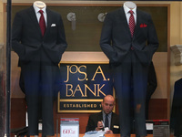 An employee works inside a Jos. A. Bank retail store in San Francisco. The parent company Tailored Brands earlier said it would close up to 500 stores and cut 20% of corporate jobs.