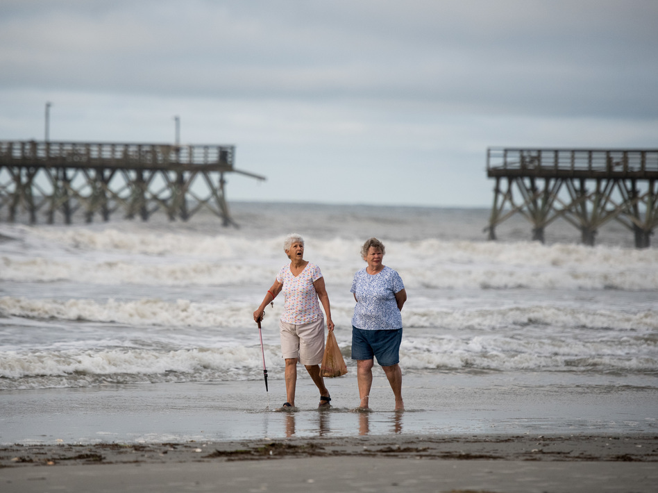 Mary McCants (left) and Amy Garrett walk near a damaged pier the morning after Hurricane Isaias came through late Monday night in North Myrtle Beach, S.C. Hurricane Isaias was downgraded to a tropical storm Tuesday after making landfall overnight as a Category 1 hurricane in North Carolina. (Sean Rayford/Getty Images)