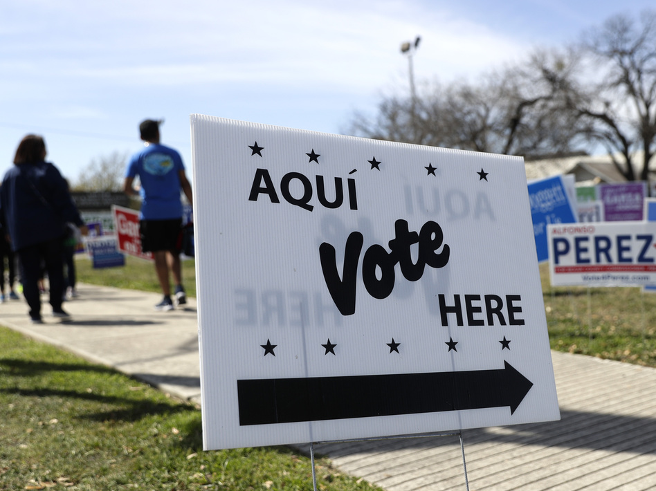 Pedestrians pass signs near a polling site in San Antonio in February. (Eric Gay/AP)