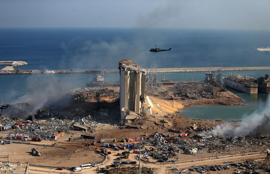 A helicopter hovers over damaged grain silos in Beirut's port on Wednesday, one day after a powerful explosion tore through Lebanon's capital. (STR/AFP via Getty Images)