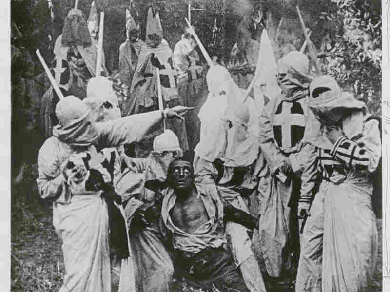 """Black and white photograph of a group of Klansmen surrounding freedman """"Gus"""" (played by white actor Walter Long in blackface) in a scene from D.W. Griffith's 1915 film, """"The Birth of a Nation""""."""