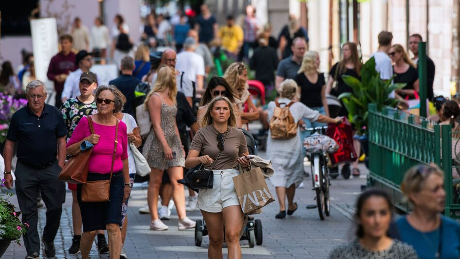 People walk in Stockholm on July 27, most without the face masks that have become common on the streets of many other countries as a method of fighting the spread of the coronavirus. (Jonathan Nackstrand/AFP via Getty Images)