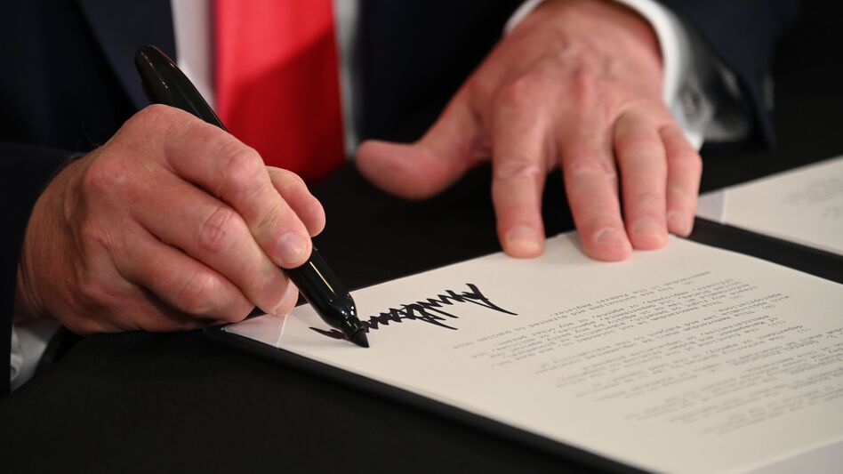 President Trump signs executive actions regarding coronavirus economic relief during a news conference in Bedminster, N.J., on Saturday. A number of lawmakers are criticizing the measures' substance and constitutionality. (Jim Watson /AFP via Getty Images)
