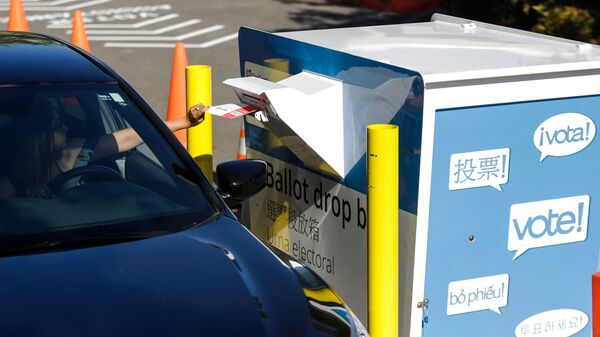 A voter inserts a ballot in a drive-up drop box last week in Renton, Wash., in that state