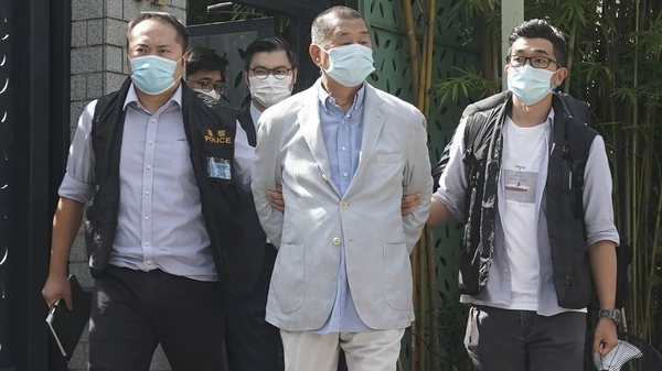 Hong Kong media tycoon Jimmy Lai, center, is arrested by police officers at his home in Hong Kong on Monday. Hong Kong police arrested Lai and raided the publisher