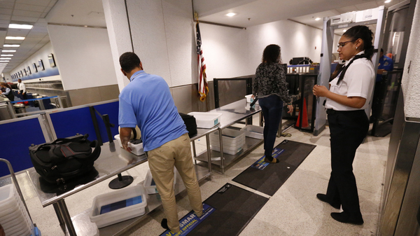 A Transportation Security Administration officer watches as travelers put their items through an X-ray machine in 2017 at Miami International Airport. The TSA says it