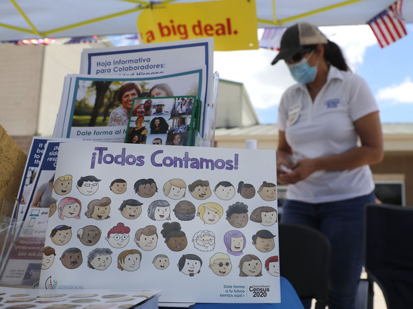 U.S. Census Bureau worker Marisela Gonzales stands by a display of books and flyers about the 2020 census at a walk-up counting site in Greenville, Texas, in July. The bureau's employees are under a time crunch to try to complete the national head count after the agency announced that counting will end a month early.