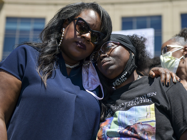 Elijah McClain's mother, Sheneen McClain (right), gets a hug from Colorado state Rep. Leslie Herod in June as they stand with protesters outside the Aurora, Colo., police headquarters. On Tuesday, Sheneen McClain and Lawayne Mosley filed a federal civil rights lawsuit in their son's death.