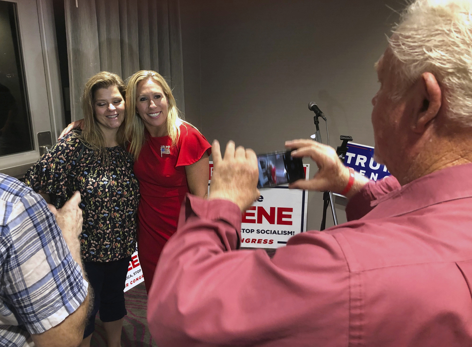 Marjorie Taylor Greene (right) is likely to bring a far-right conspiracy theory to the House of Representatives next year. (Mike Stewart/AP)