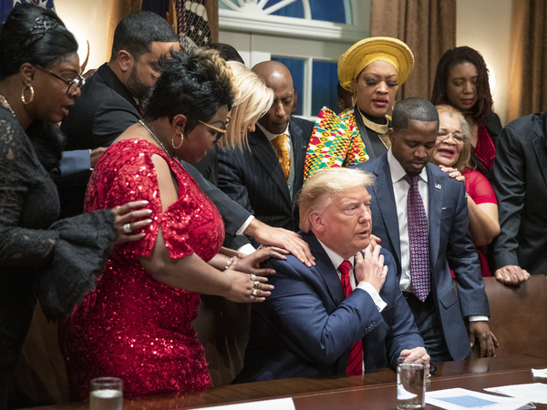 Black leaders say a prayer with President Trump as they end a meeting in the Cabinet Room of the White House on Feb. 27, 2020.