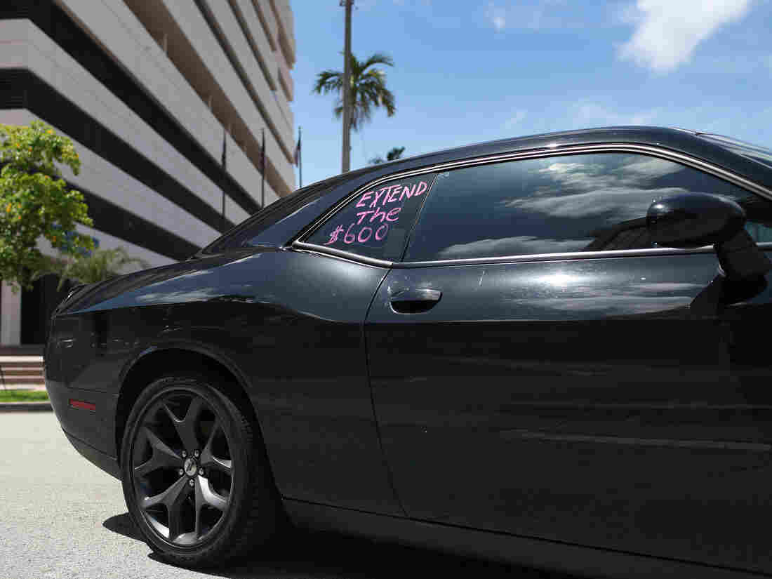 """A car with """"extend the $600!"""" written on a window participates in a protest on July 16, 2020 in Miami Springs, Florida."""
