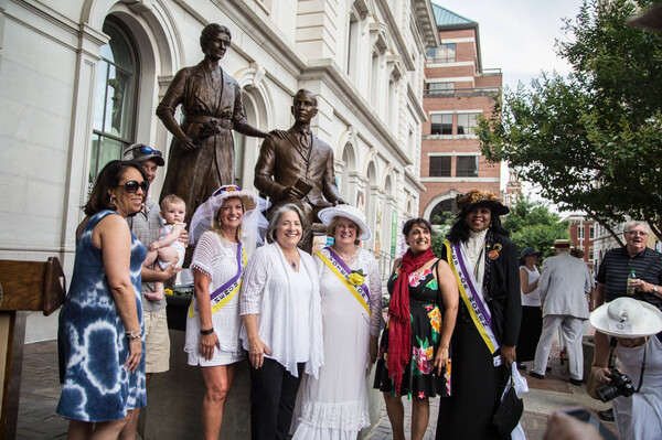 Suffrage Coalition President Wanda Sobieski (third from right, in suffrage regalia) and other coalition members pose with the statue of Febb and Harry Burn at the unveiling of the Burn Memorial in Knoxville, Tenn., in June 2018.
