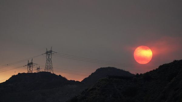 The sun sets through smoke created by the Ranch Fire on Aug. 13, 2020, in Azusa, Calif. A heat wave has prompted electrical providers to issue the first rolling blackouts in the state since 2001.