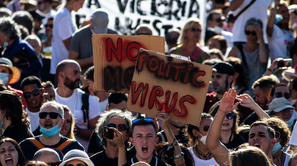 People holding placards and shouting slogans protest Sunday in Madrid against the mandatory use of face masks and other measures adopted by the Spanish government to prevent the spread of the coronavirus.
