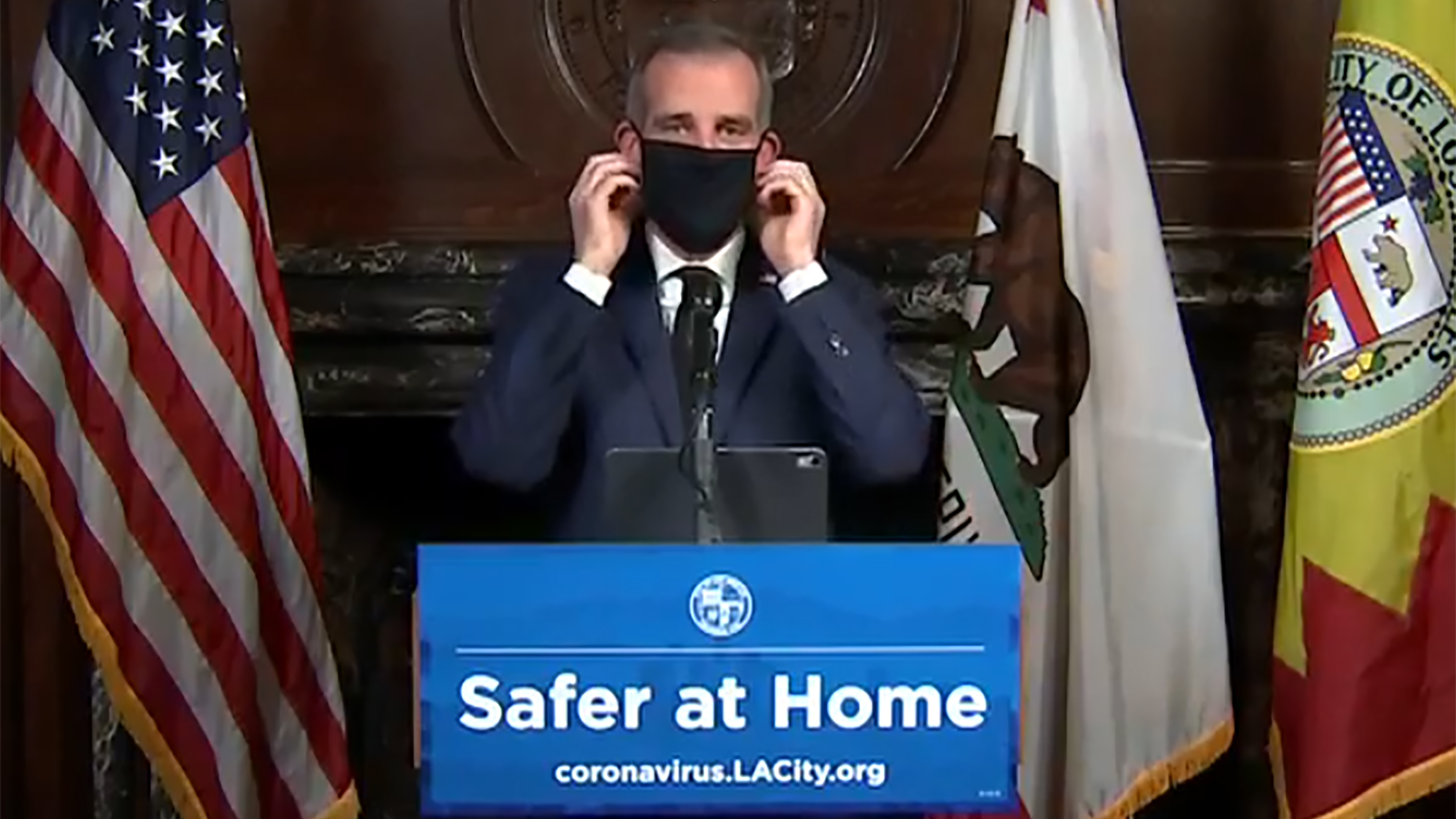 Los Angeles Mayor Eric Garcetti puts on a face mask during a news briefing in April.