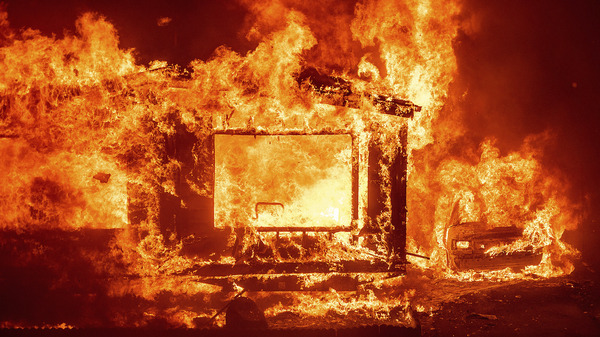 A mobile home and car burn at Spanish Flat Mobile Villa as the LNU Lightning Complex fires tear through unincorporated Napa County, Calif., on Tuesday.